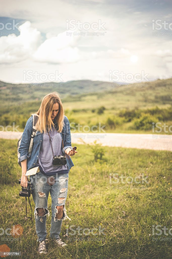 Young woman tourist looking on compass. stock photo