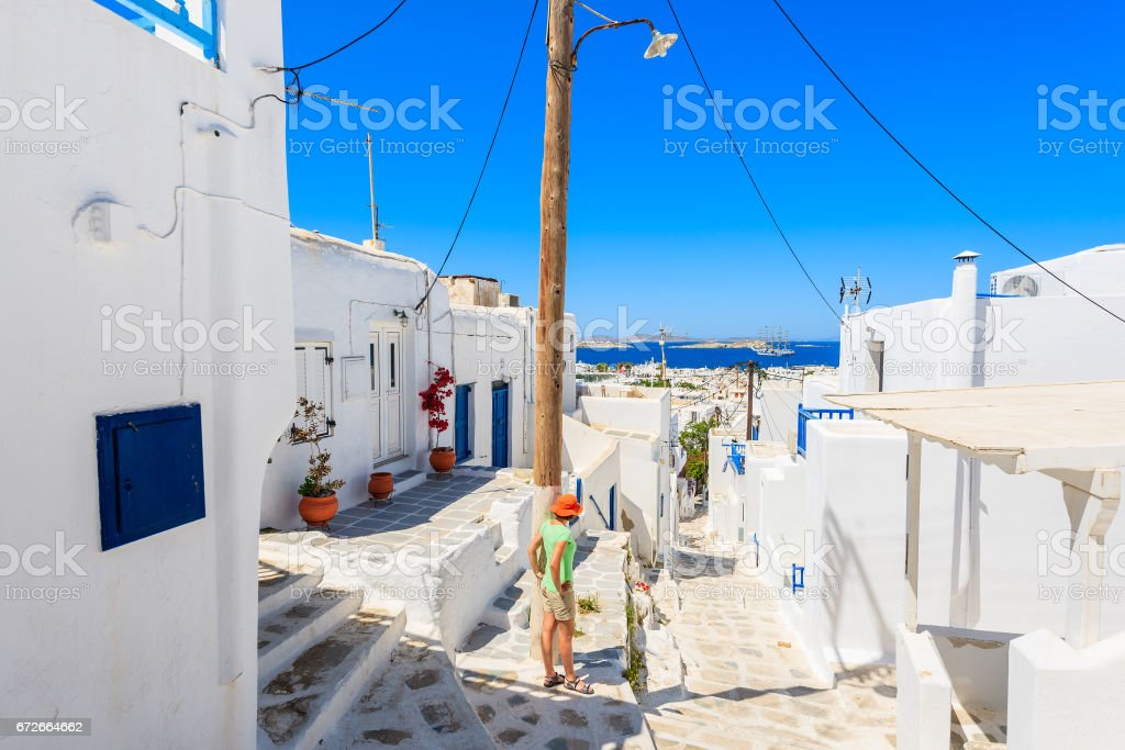 A young woman tourist standing on Mykonos town street looking at sea, Cyclades islands, Greece stock photo