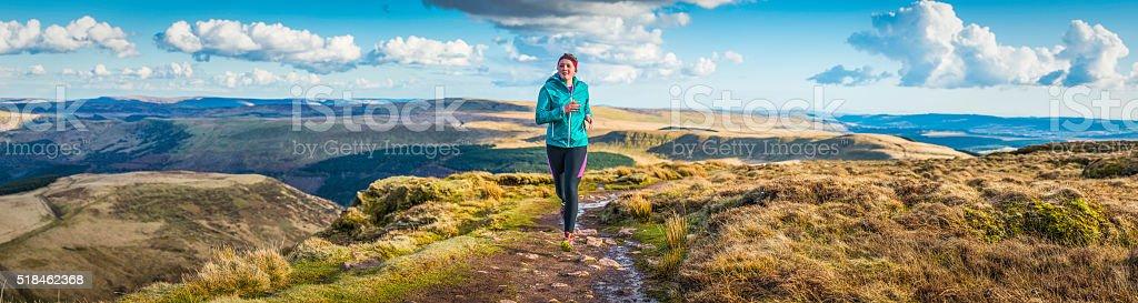 Young woman trail running along wilderness path mountain ridge panorama stock photo