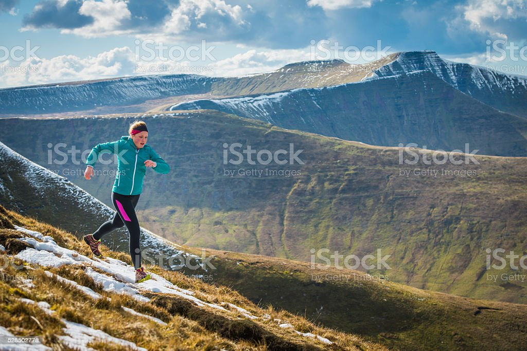 Young woman trail running on mountain ridge Brecon Beacons Wales stock photo