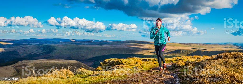 Young woman trail running over wilderness mountain ridge path panorama stock photo