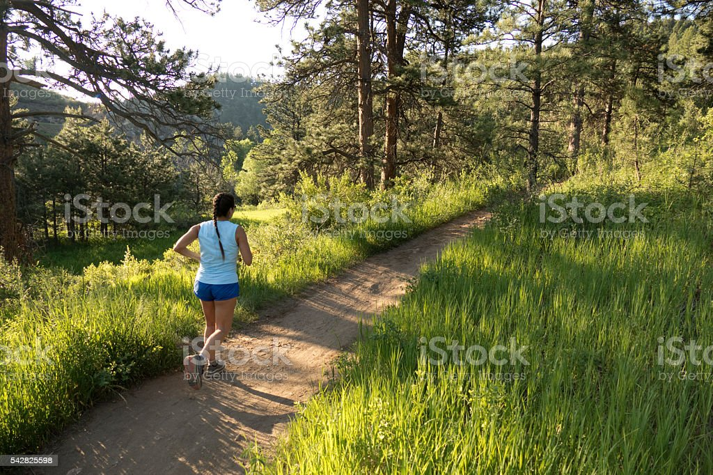Young woman trail runs Bear Creek forest Colorado Rocky Mountains stock photo