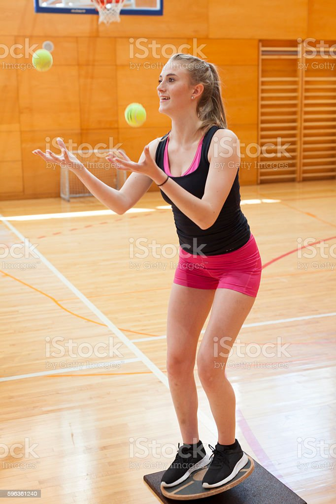 Young Woman Training Body Coordination and Equilibrium in the Gym stock photo