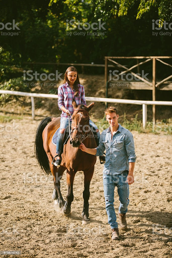 Young woman training horseback riding technique with instructor. stock photo