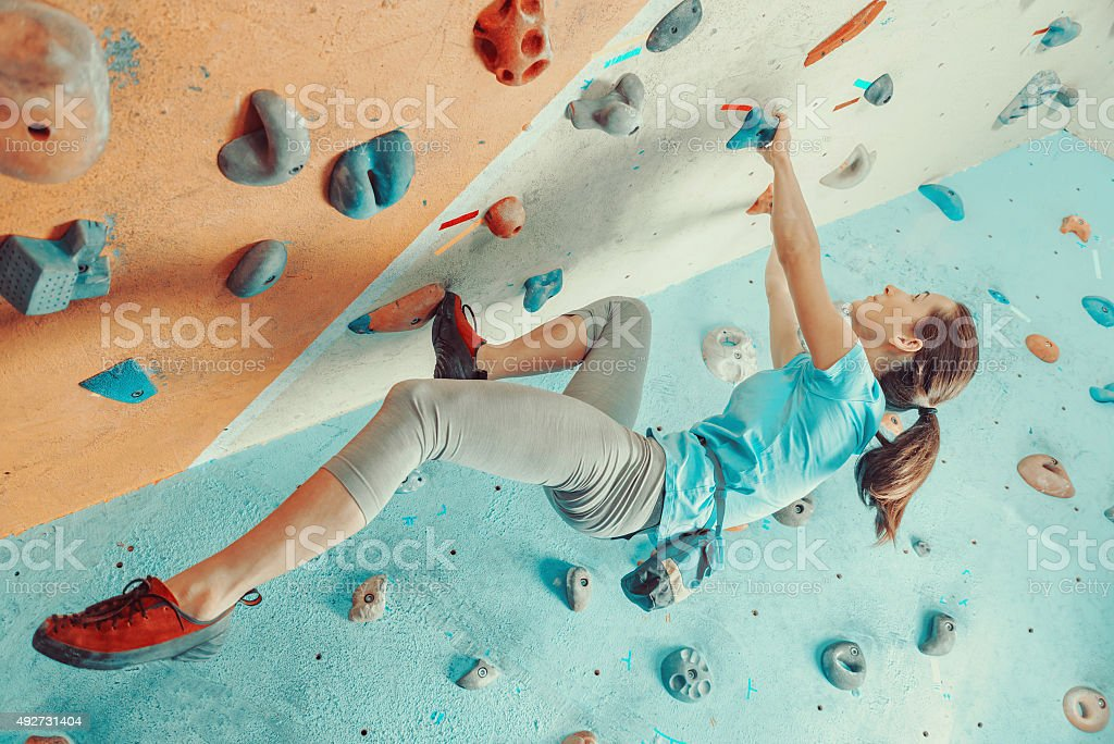 Young woman training in climbing gym stock photo