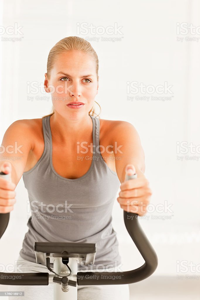 Young woman training on an exercise bike royalty-free stock photo