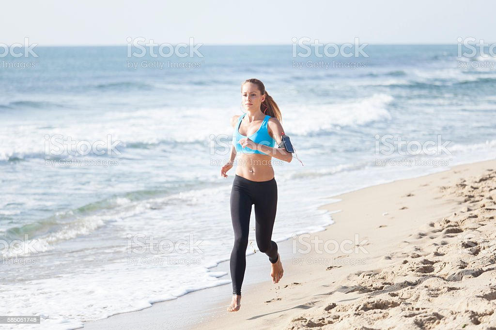 Young woman training on the beach stock photo