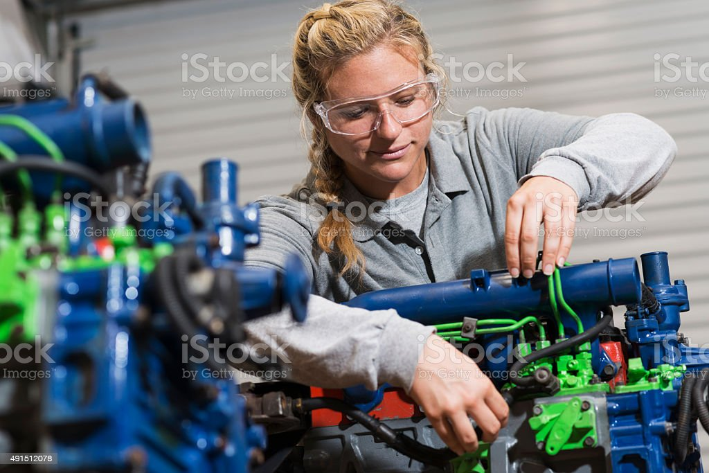 Young woman training to be auto mechanic stock photo
