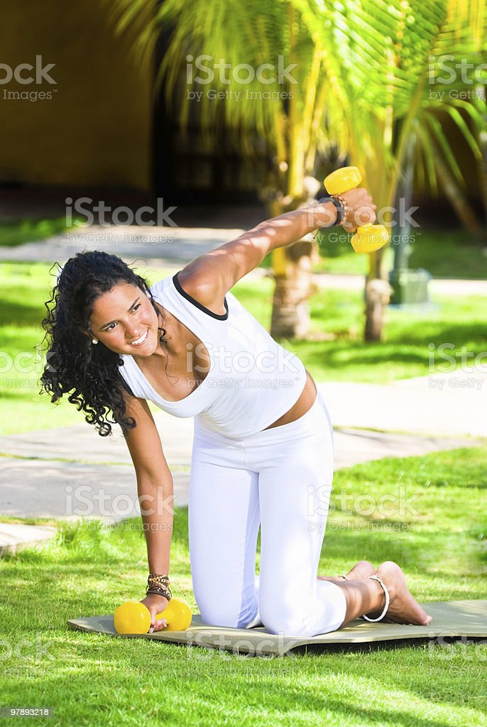 Young woman training with dumbbells on a tropical Spa royalty-free stock photo
