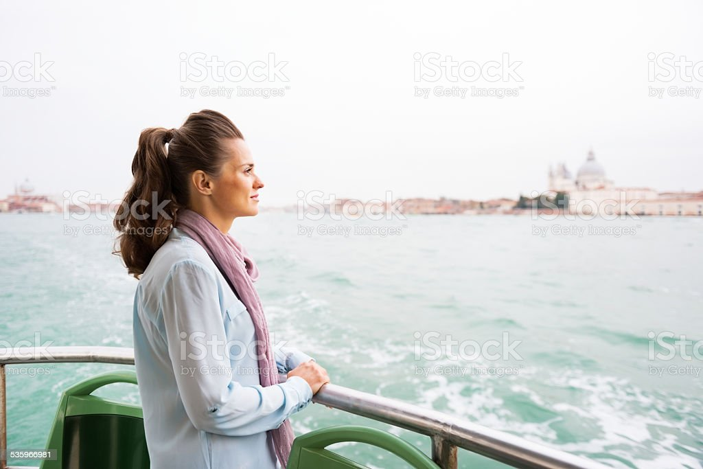 Young woman travel by vaporetto in venice, italy stock photo