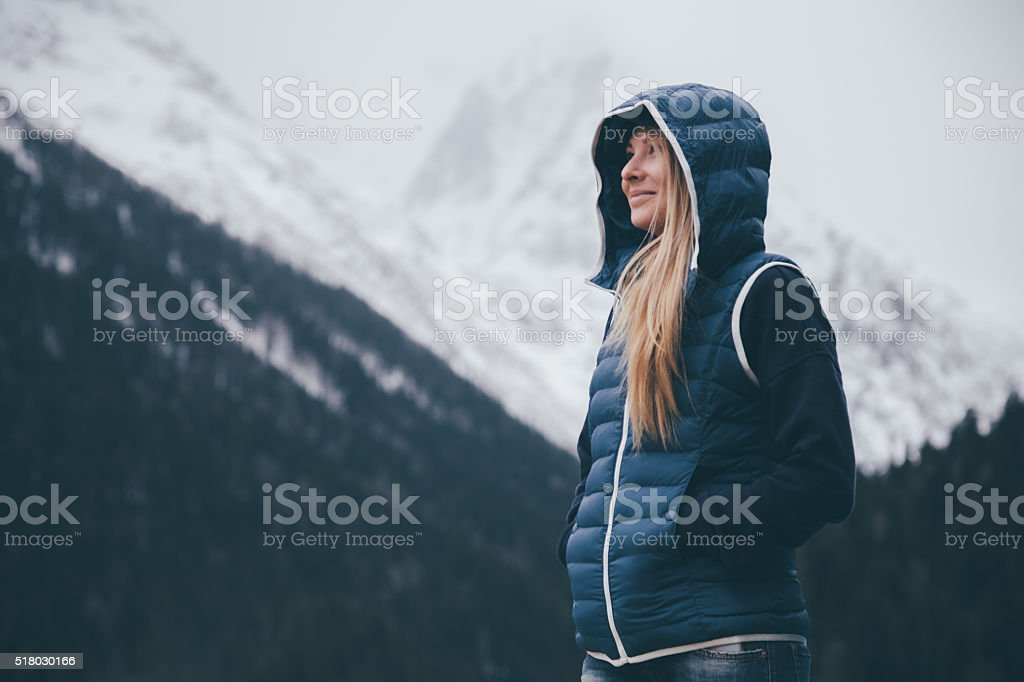 Young woman traveler looks on mountains stock photo