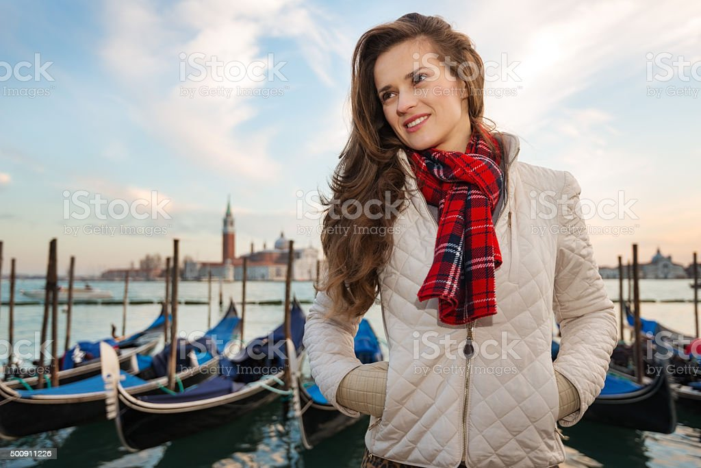 Young woman traveler standing on embankment in Venice, Italy stock photo