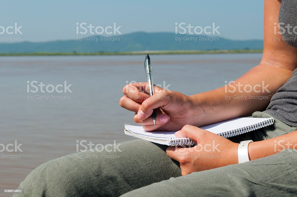 Young woman traveler writing in notebook stock photo