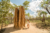 Young woman traveling stands by a huge termite mound