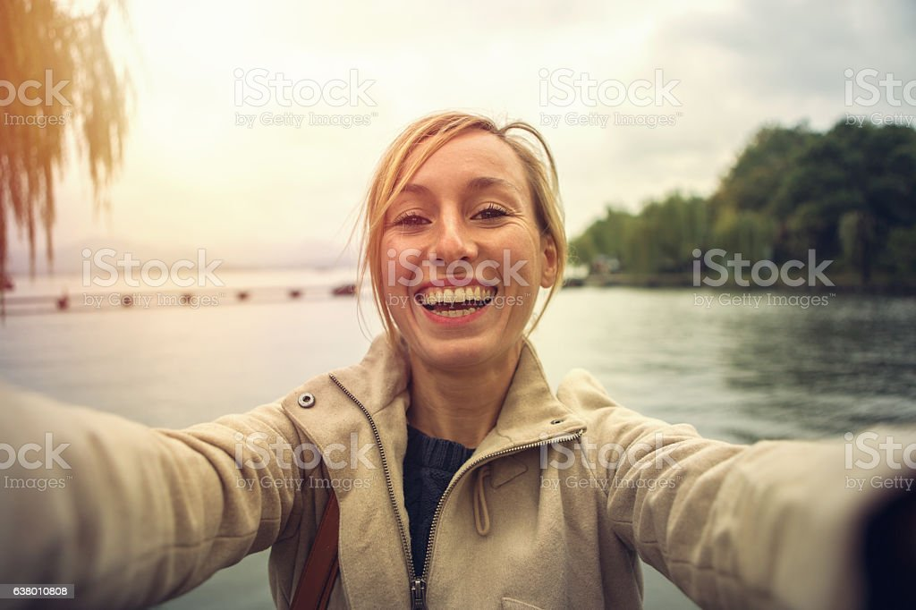 Young woman traveling takes a selfie portrait by the lake stock photo