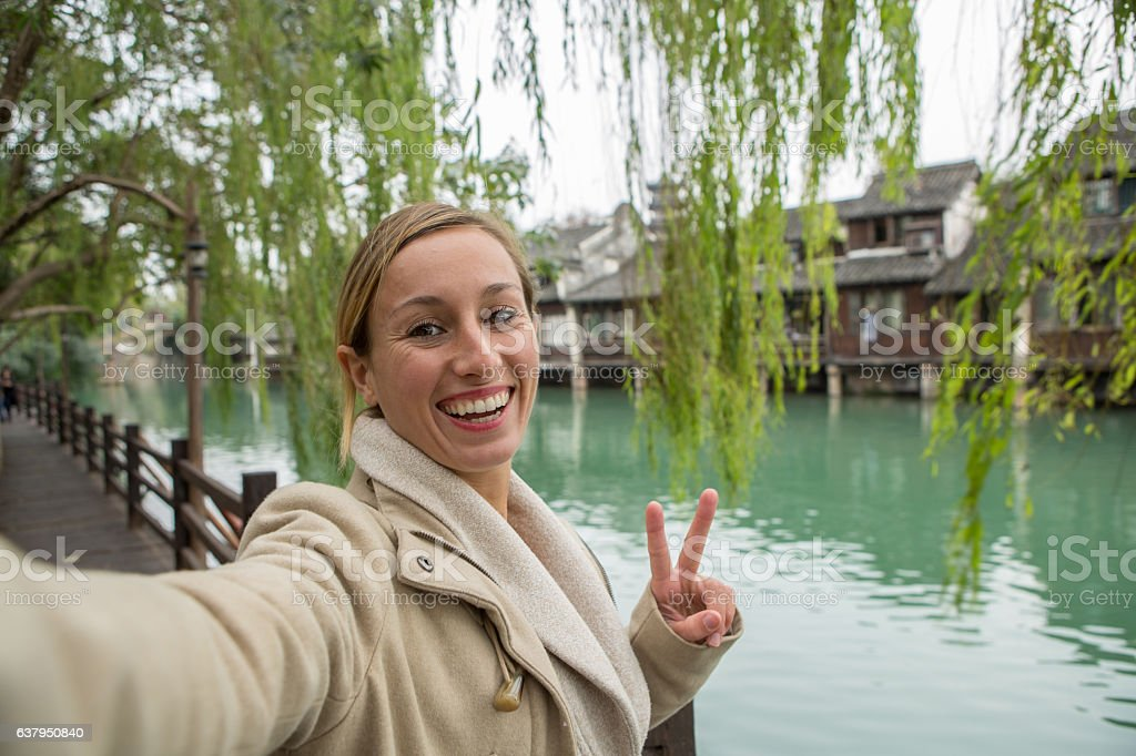 Young woman traveling takes selfie portrait in Chinese village stock photo
