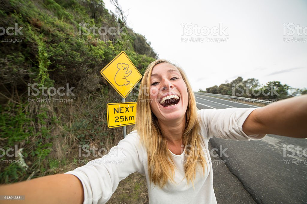 Young woman traveling takes selfie portrait with koala crossing sign stock photo