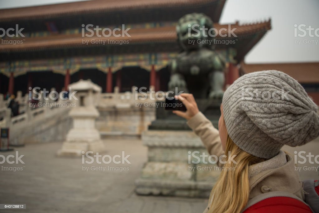 Young woman traveling takes smart phone picture of Forbidden City stock photo
