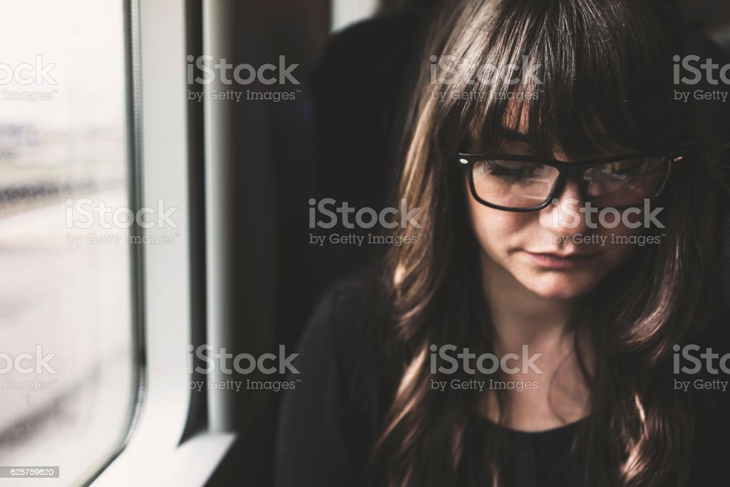Young woman travelling in train, sitting inside vehicle stock photo