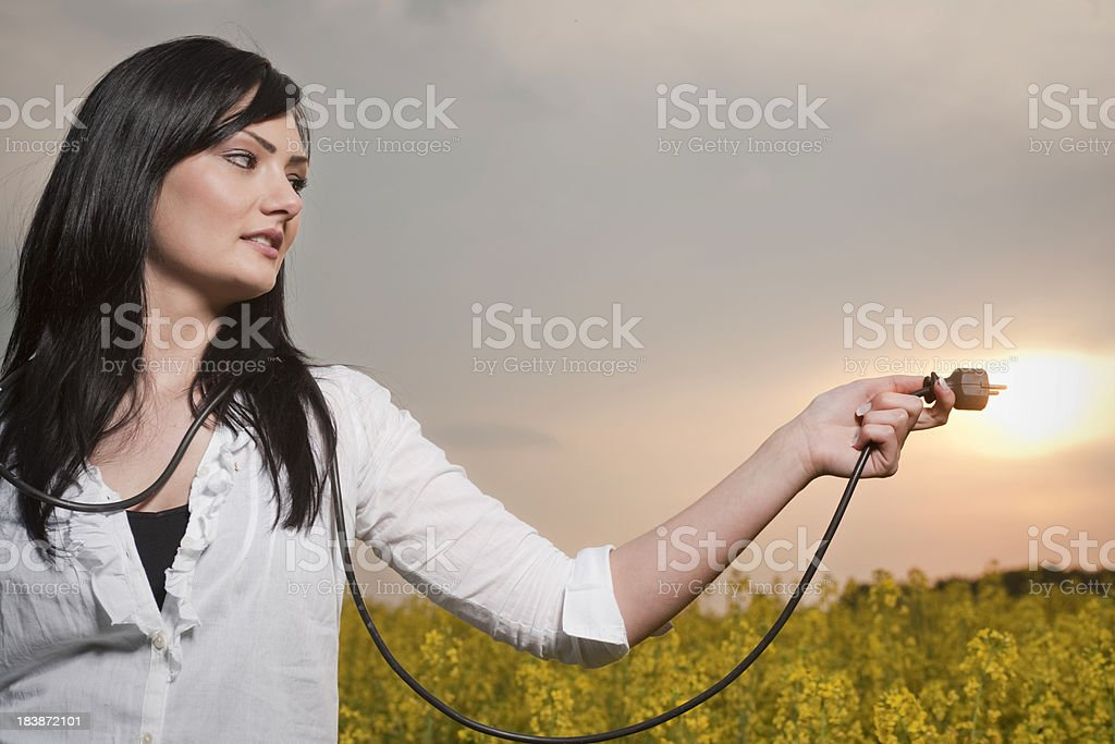Young woman tries to put electrical plug into the sun royalty-free stock photo