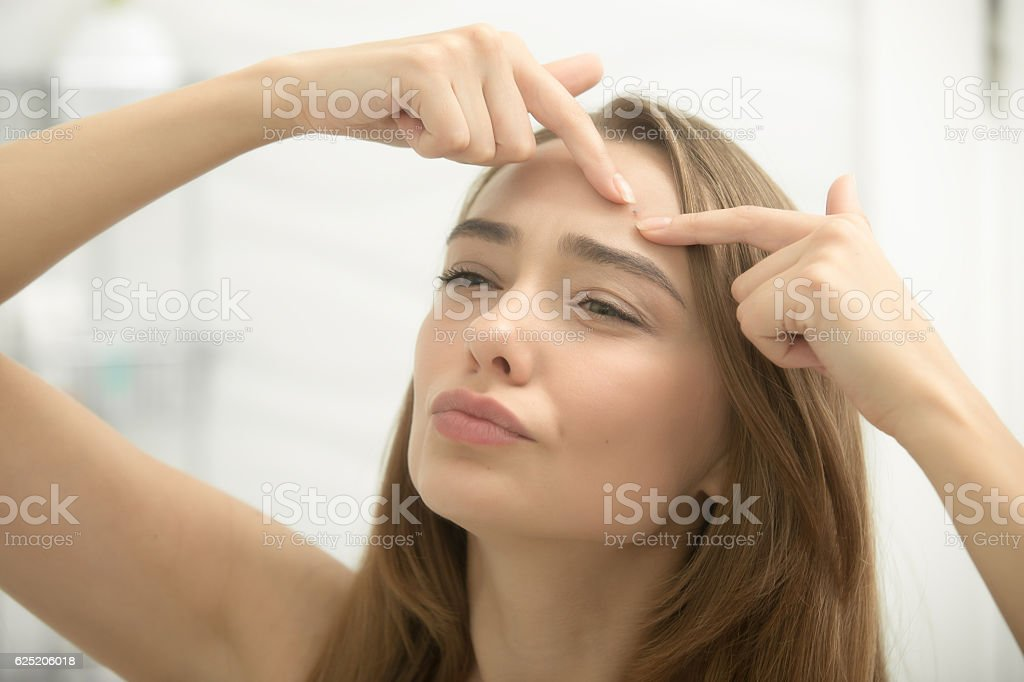 Young woman troubled checking wrinkles on her forehead stock photo