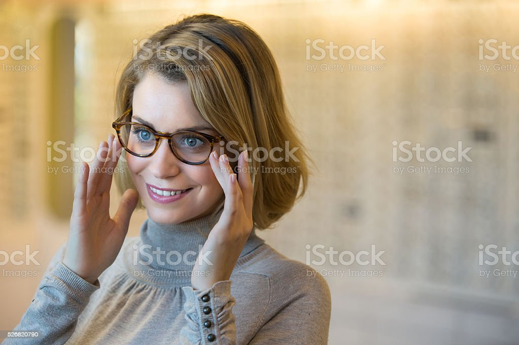 Young woman trying on glasses stock photo