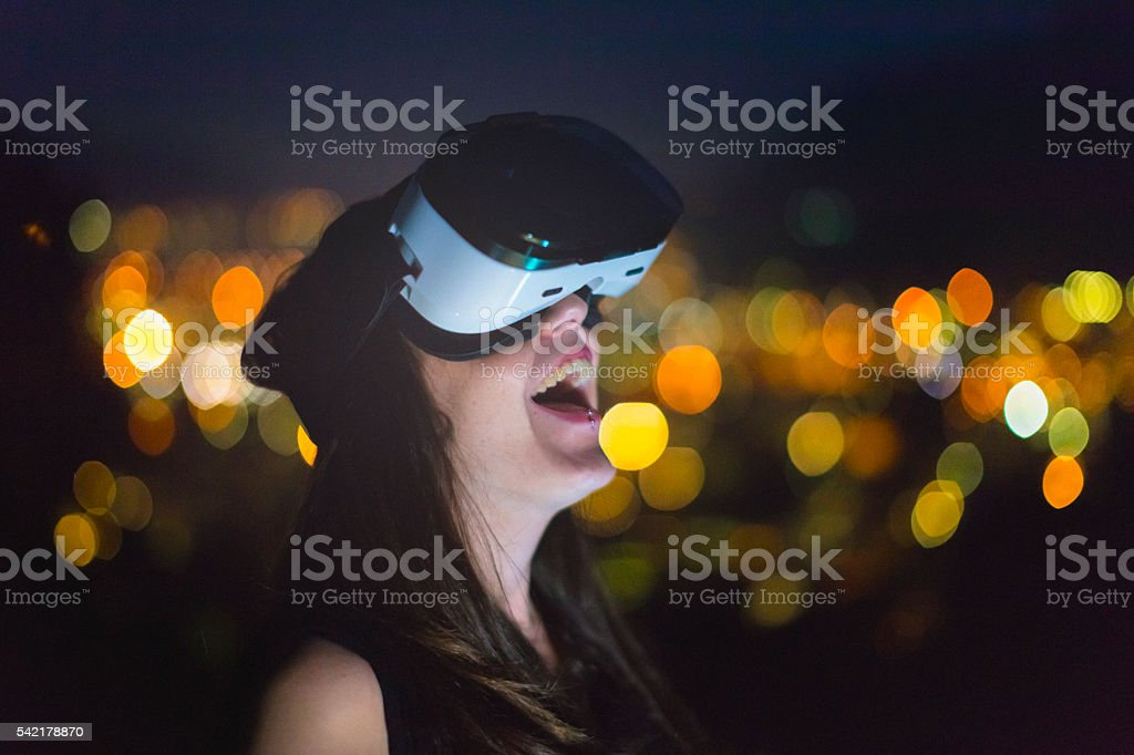 Young woman trying Virtual Reality Simulator at night stock photo