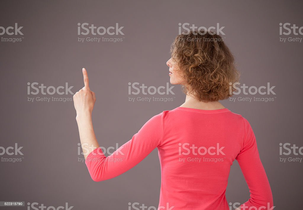 Young woman turning back and indicating something up stock photo