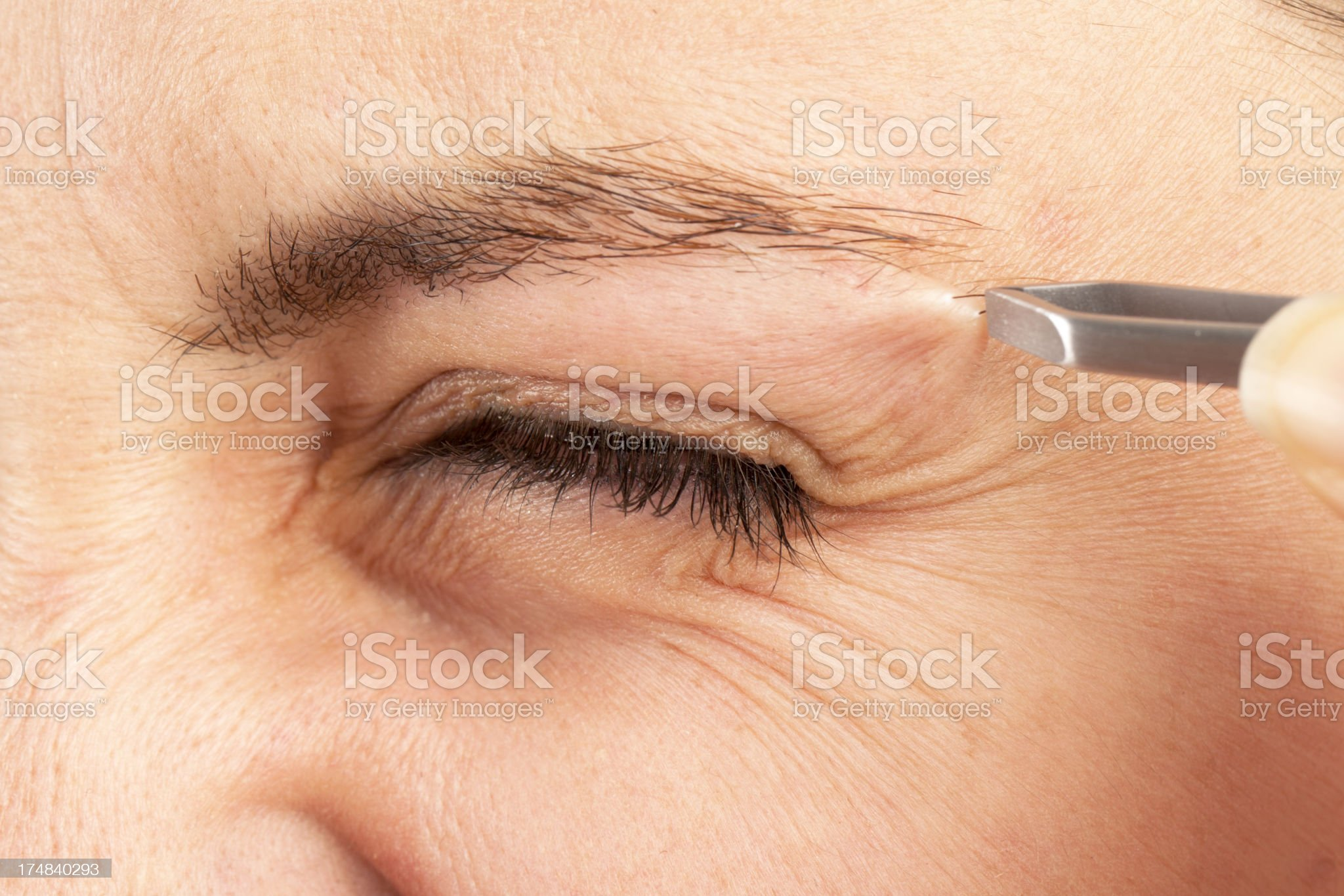 Young Woman Tweezing Her Eyebrows royalty-free stock photo