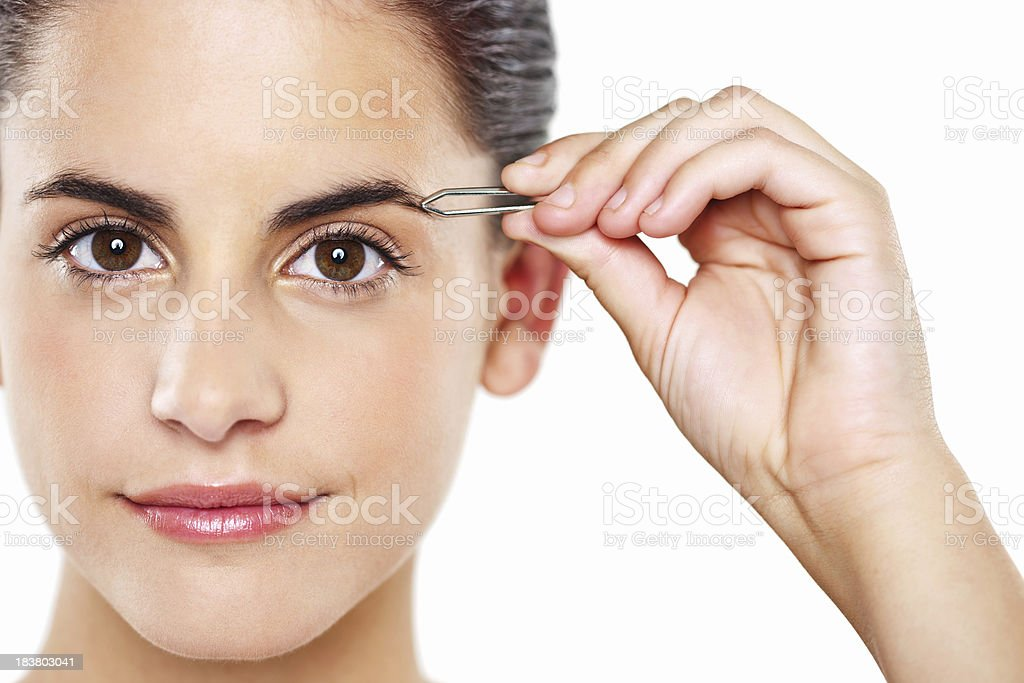 Young Woman Tweezing Her Eyebrows stock photo