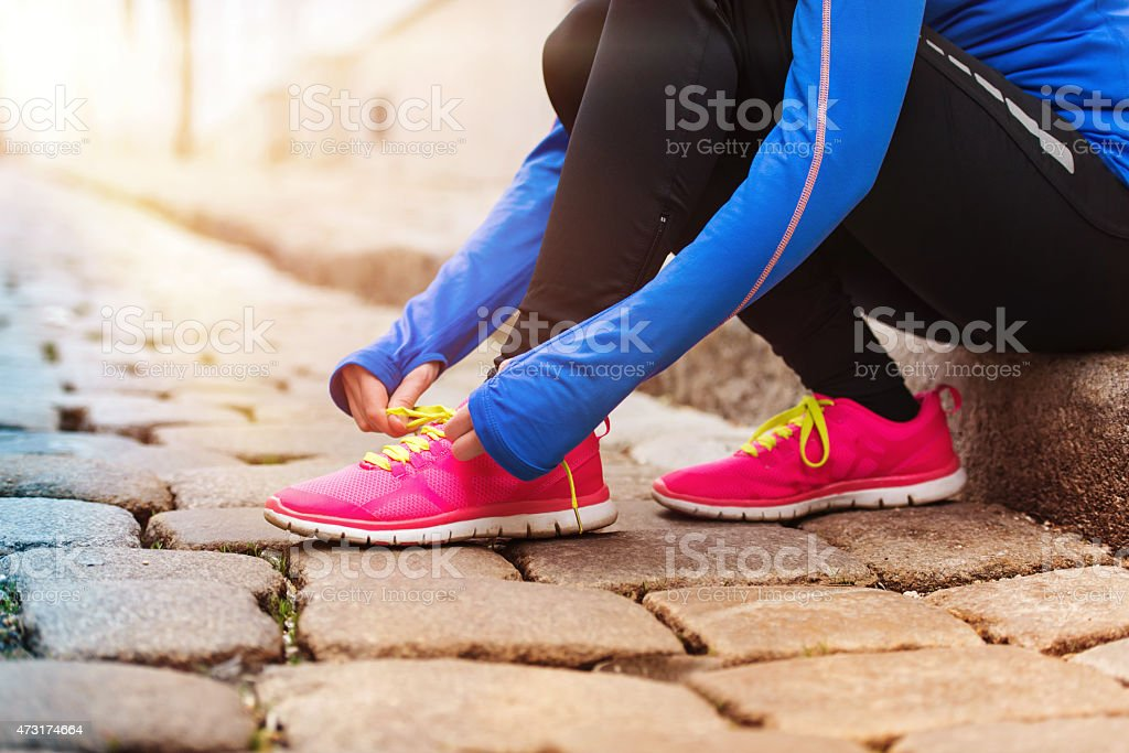 Young woman tying her pink sneakers to get ready for a run stock photo