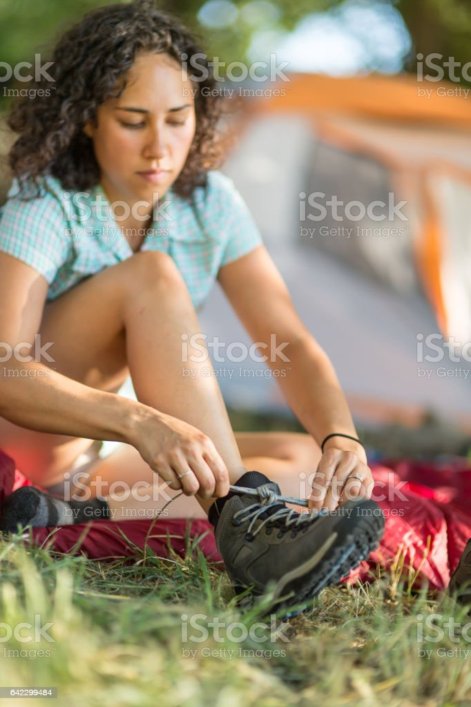 Young woman tying shoe outside tent stock photo