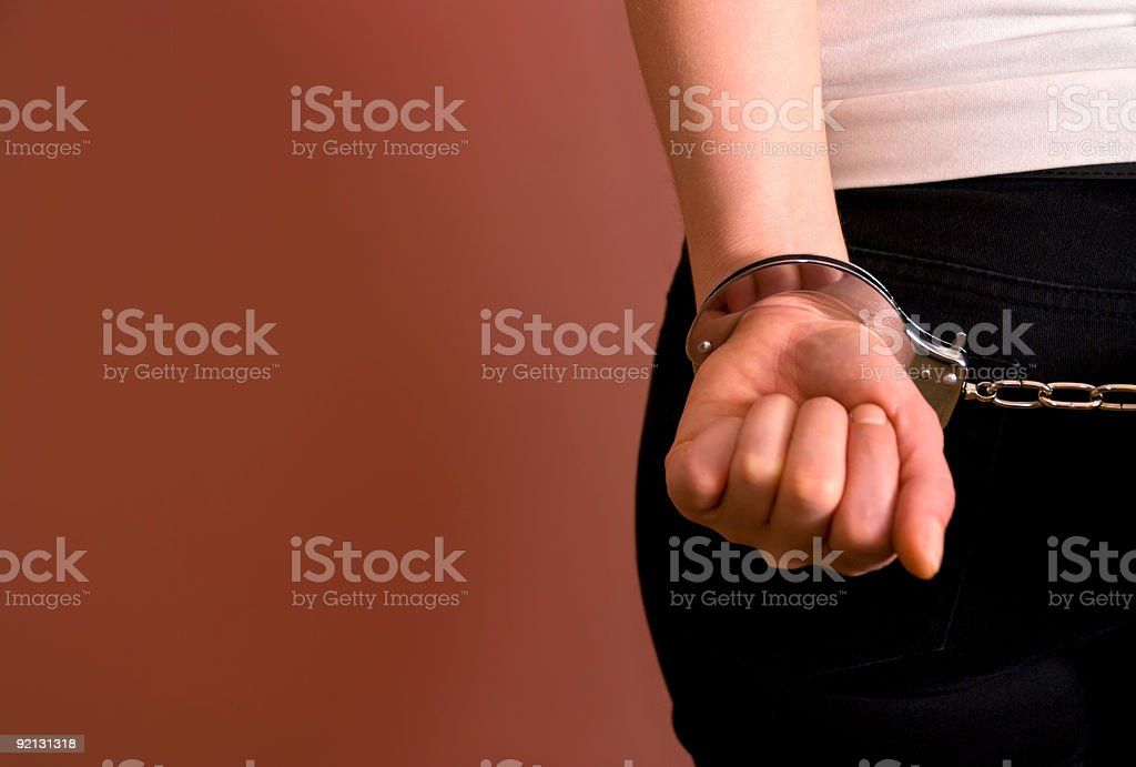 A young woman, under arrest and being taken into a cell stock photo