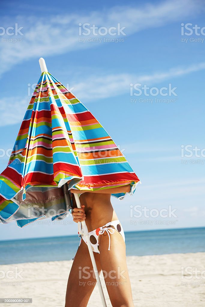Young woman under closed beach umbrella, close-up royalty-free stock photo