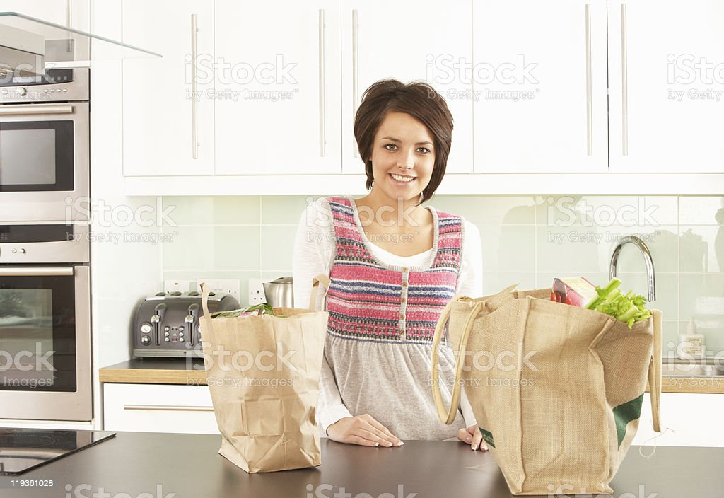 Young Woman Unpacking Shopping In Modern Kitchen stock photo