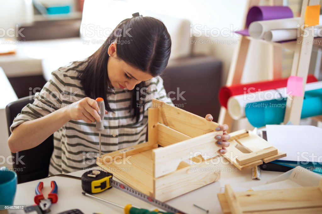 Young woman uses the screwdriver at home stock photo