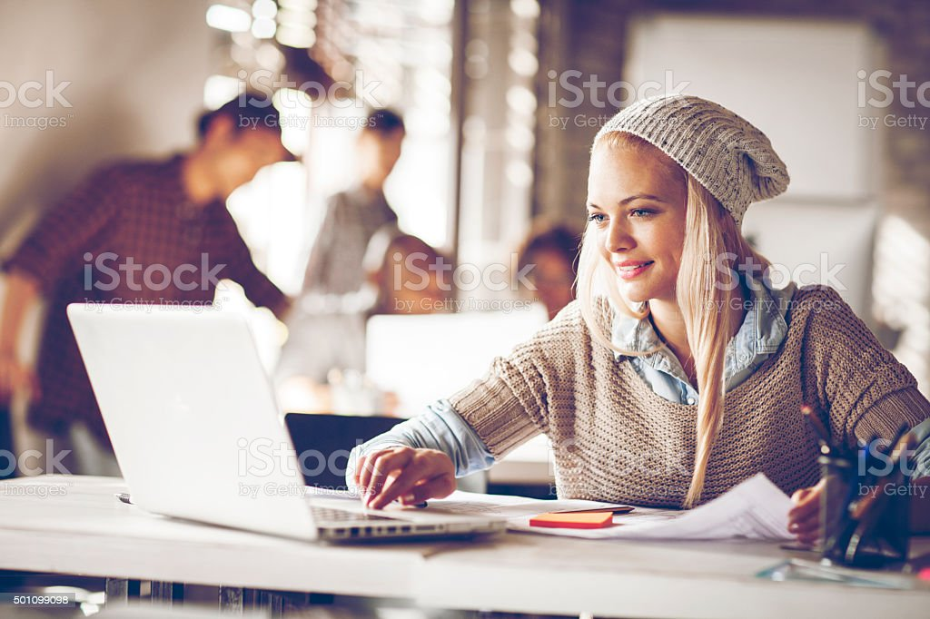 Young woman usign laptop in office stock photo