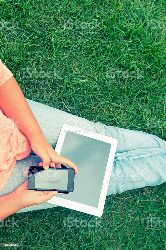 Young woman using a digital tablet and mobile phone royalty-free stock photo