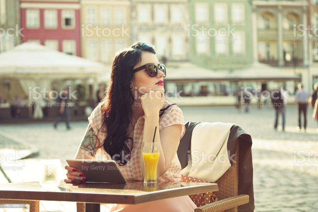 Young woman using a digital tablet in the outdoor restaurant stock photo