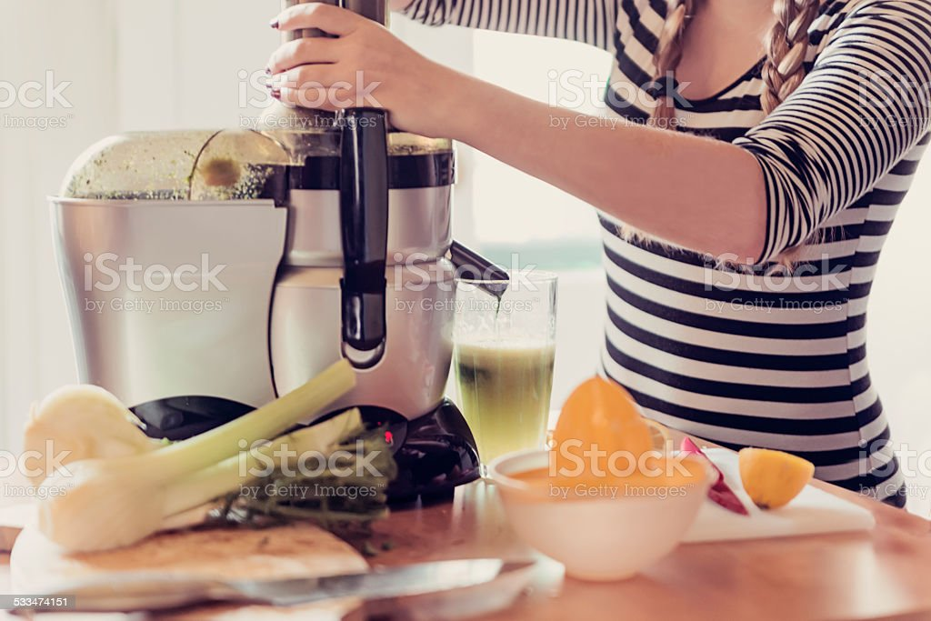 Young woman using a juicer in a small appartement kitchen. stock photo