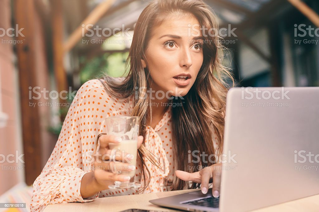 Young woman using a laptop at the cafe stock photo