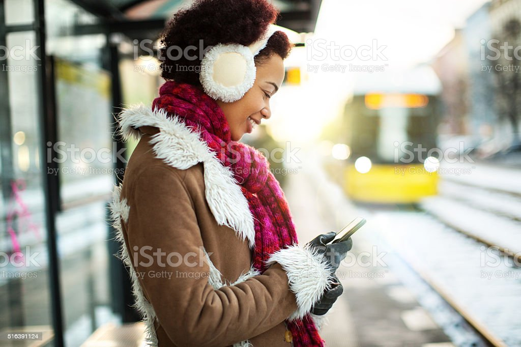 Young woman using a mobile phone at train station stock photo
