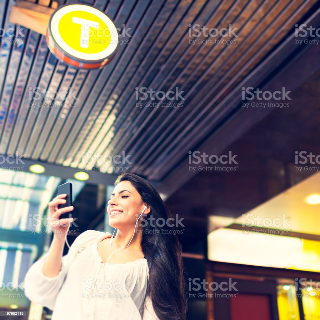 Young woman using a phone at train station stock photo