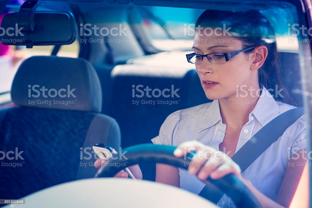 Young Woman Using a Phone While Driving a Car stock photo