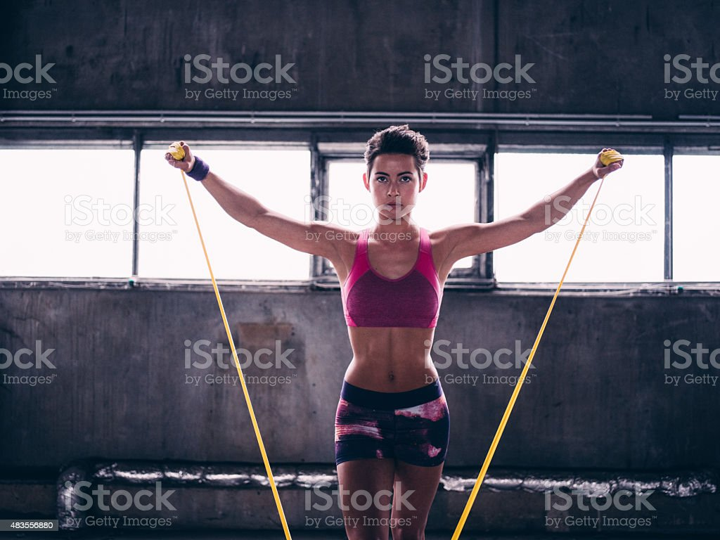 Young woman using a resistance band in gym exercises stock photo