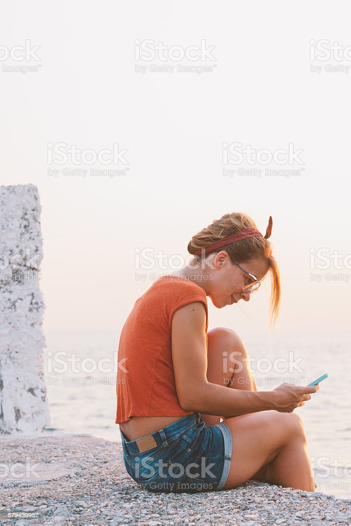 Young woman using a smartphone near the sea stock photo