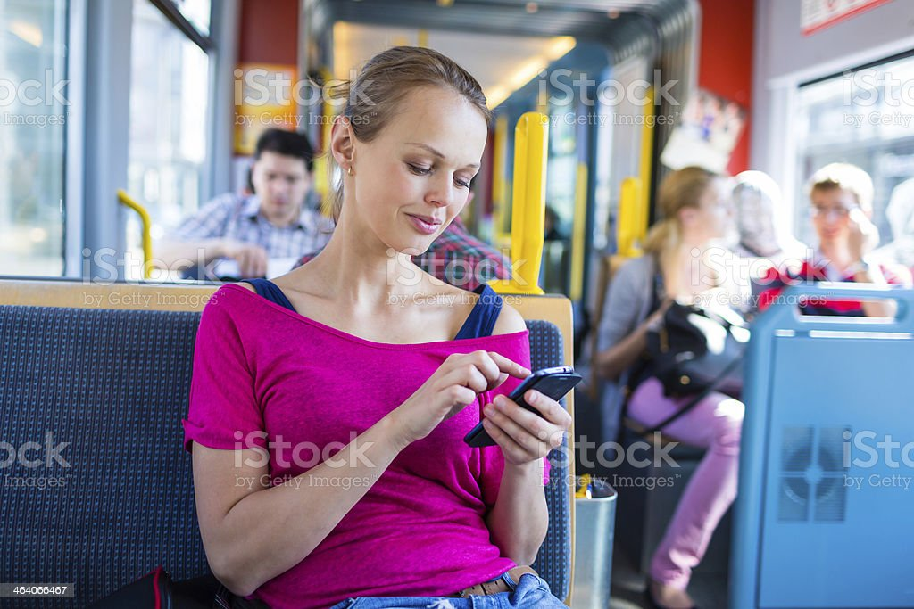 Young woman using a smartphone on a tram stock photo