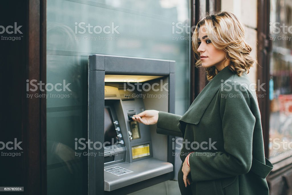 Young woman using ATM stock photo