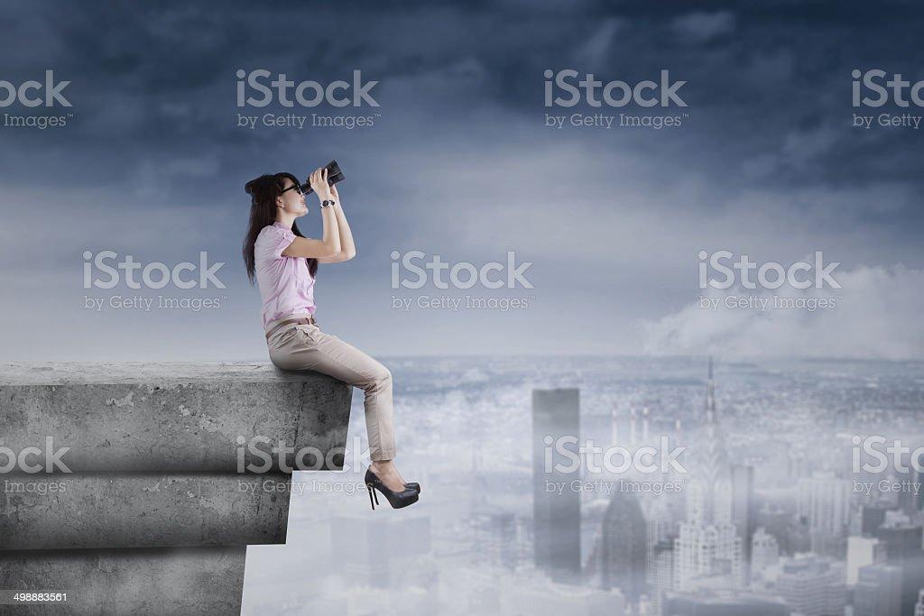 Young woman using binoculars on rooftop stock photo