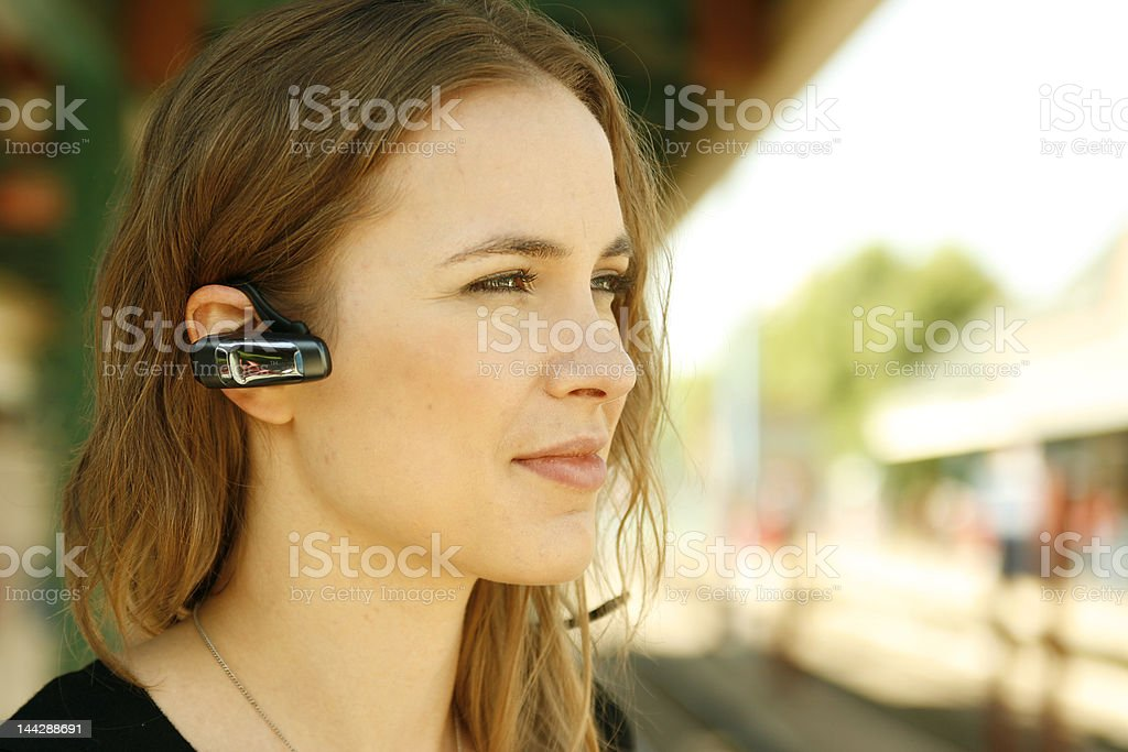Young woman using bluetooth headset stock photo